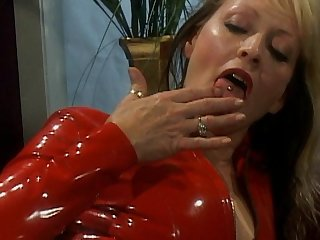 Two ladies in latex are spanking each other and playing with trimmed pussies on the camera
