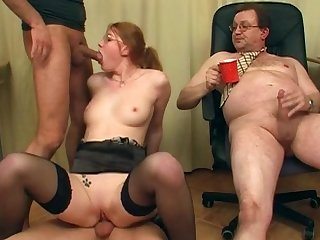 Hardcore beauty in glasses is sucking two small cocks in the office and getting cum on her face