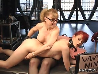 Nina Hartley wearing stockings and glasses is fucking her lesbian slave with a strapon in this femdom video.