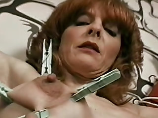He ties her up, he attaches clothes pins to her tits for pain and he gags the hot redhead.