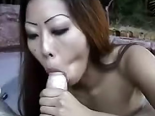 Redhead and asian cock sucker with long hair is sucking big shaft on her knees outdoors