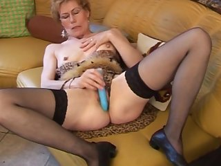 Awesome granny model with pretty face is lying on the sofa and touching her lovely pussy with pleasure