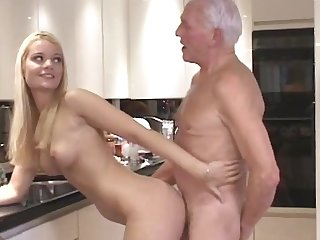 Young and beautiful blonde babe with natural tits and slender body fucked by old man at the kitchen.